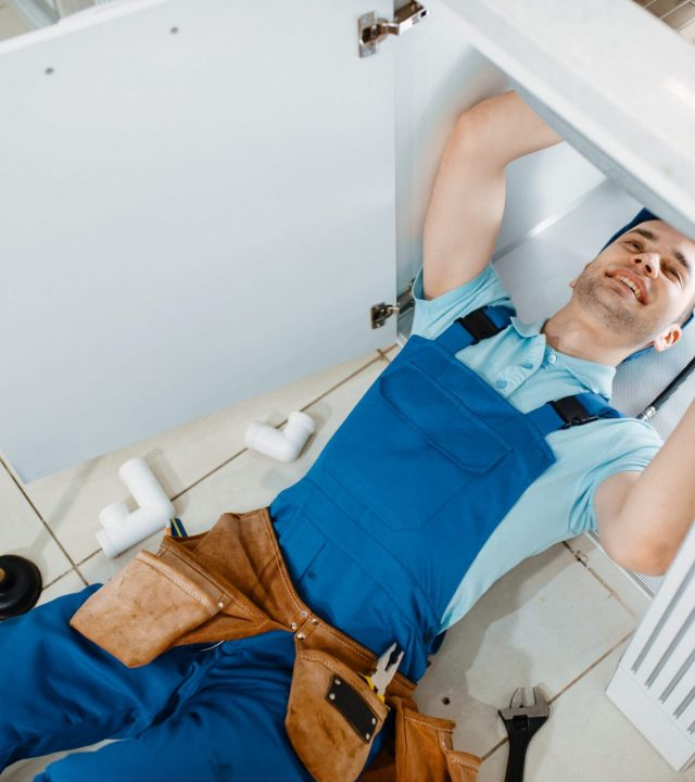 plumber-in-uniform-installing-drain-pipe-top-view-GKUZZ9Q-scaled-1.jpg